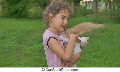 brunette girl holding kitten in her arms love outdoors -...