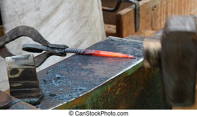 Blacksmith forging red hot iron