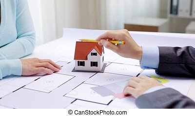 woman and architect discussing blueprint of house -...