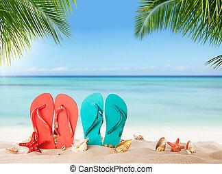 Summer flipflops on sandy beach, blur sea on background...
