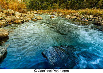 Reshi River water flowing on rocks at dawn, Sikkim, India -...