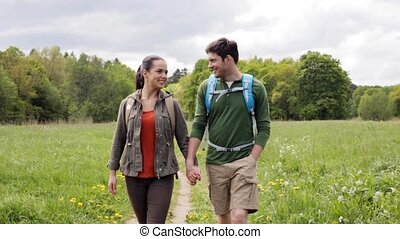 happy couple with backpacks hiking outdoors 3 - travel,...