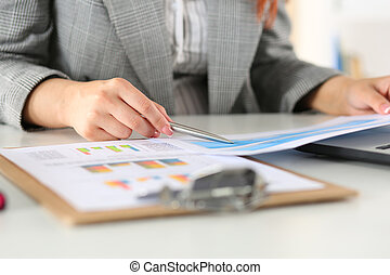 Businesswoman looking at graphics Manager or auditor reading...