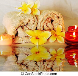spa image of frangipani flowers candles and towels