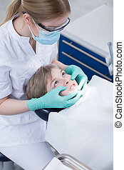 Not willing to open mouth - Young boy sitting on a dentist's...
