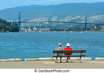 Lions Gate Bridge - An old couple sit at waterfront in...