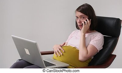 Pregnant woman using laptop for solves the problem - A...
