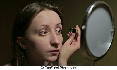 Young woman doing makeup