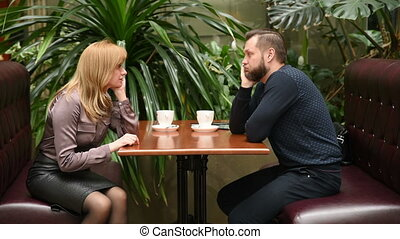 man and woman in a cafe. drink coffee. a business meeting