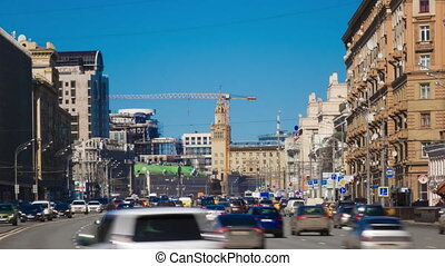 Busy sunny city traffic time lapse with distant crane....
