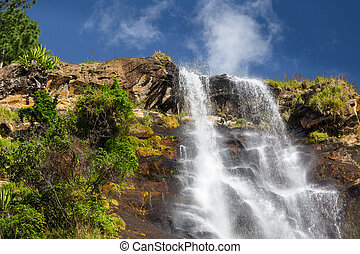 Waterfall from the hill with blue sky on the background