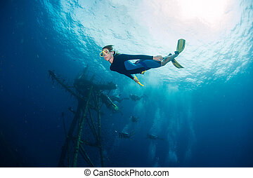 Lady diver - Free diver on depth with ship wreck on the...