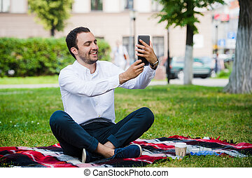 Modern young hispanic man taking a selfie at the park, with his tablet.