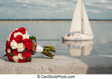 Wedding bridal bouquet with res and white roses against the background of theyacht. Wedding concept