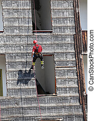 climber firefighter rappelling the wall - firefighter...