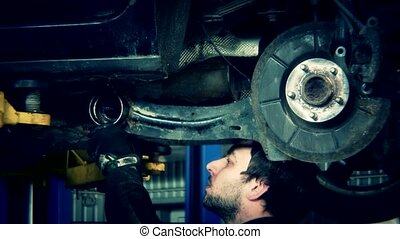 Mechanic renew brake system of a vehicle on a car lift. Zoom...