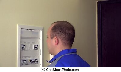 Man in blue uniform turn on circuit breakers on panel box at...