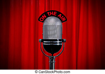 Microphone on stage with spotlight on red curtain - Retro...
