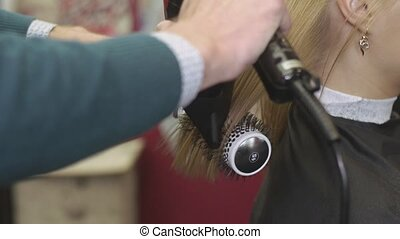 Male barber pull tips of blonde girl by comb and hairdryer...
