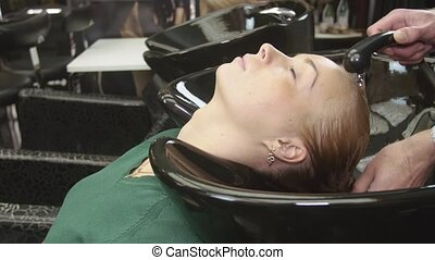 Professional hairdresser wash hair of blonde young girl in beauty saloon in special bath. Hair care