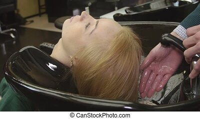 Professional barber tune water to wash hair of blonde young girl in beauty saloon. Hair care