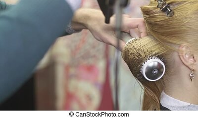Barber pull hair of blonde girl by comb and hairdryer in...