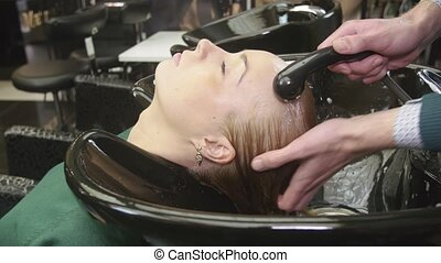 Professional barber wash hair of blonde girl by water in beauty saloon. Massage of head. Hair care