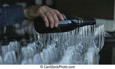 Groom pours sparkling champagne in narrow glass goblets...