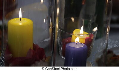 Composition of flower petals and burning candles stands on festive table