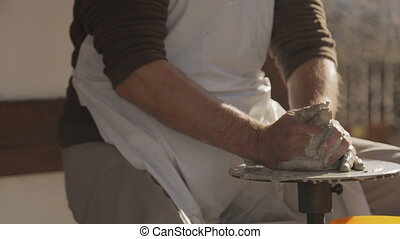 Artisan works with pottery wheel to create ceramic jug for...