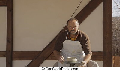 Old ceramist in white apron attentively looks in front of...