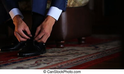Man in dark blue jacket ties laces on black patent leather shoes