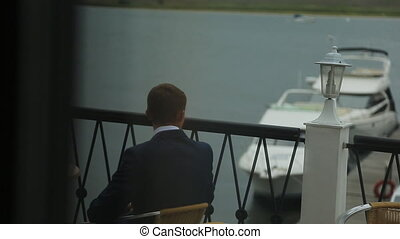 Man in black suit sits on berth awaiting for his companion....