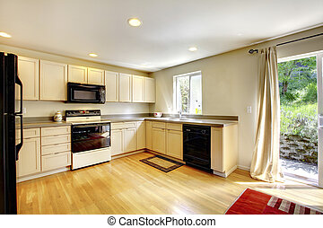 Brown wooden dining table in small kitchen room with black appliances.