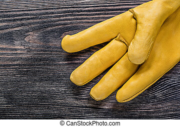 Leather protective glove on wooden board maintenance concept...
