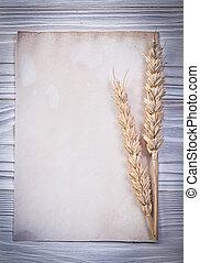 Ripe wheat ears blank vintage paper sheet on wooden board