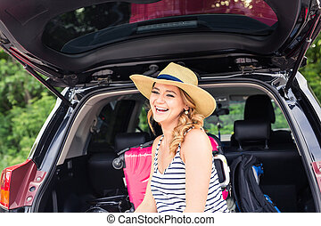 Young woman with suitcases. Vacation concept. Car trip....
