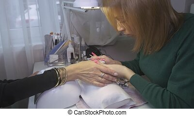 Manicurist put off shellac cover from nails of woman in...