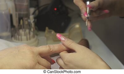 Manicurist polish nail to woman in beauty saloon by...