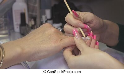 Professional manicurist put off nail cover to woman in...