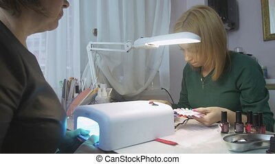Manicurist choose color of lacquer with client in beauty saloon. Hands in ultraviolet lamp. Shellac