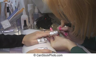 Manicurist polish surface of nails to woman by nail...