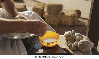 Master works on Potters wheel outside workroom in...