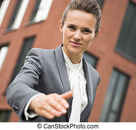 Portrait of modern business woman stretching hand for...
