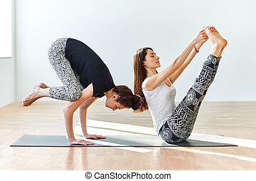 Two young women practicing yoga poses and asanas. Partner...