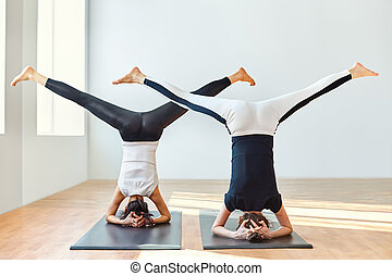 Two young women doing yoga asana open angle pose in...