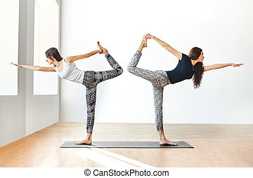 Two young women doing yoga asana lord of the dance pose....