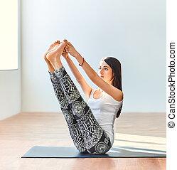 Young woman doing yoga asana both big toes pose. Ubhaya...