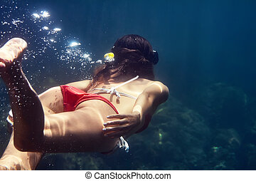 back view of woman with mask swimming underwater in tropical...