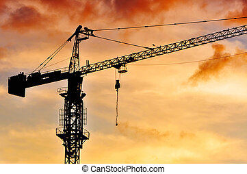 Crane - Dark silhouette of a construction crane at dusk,...